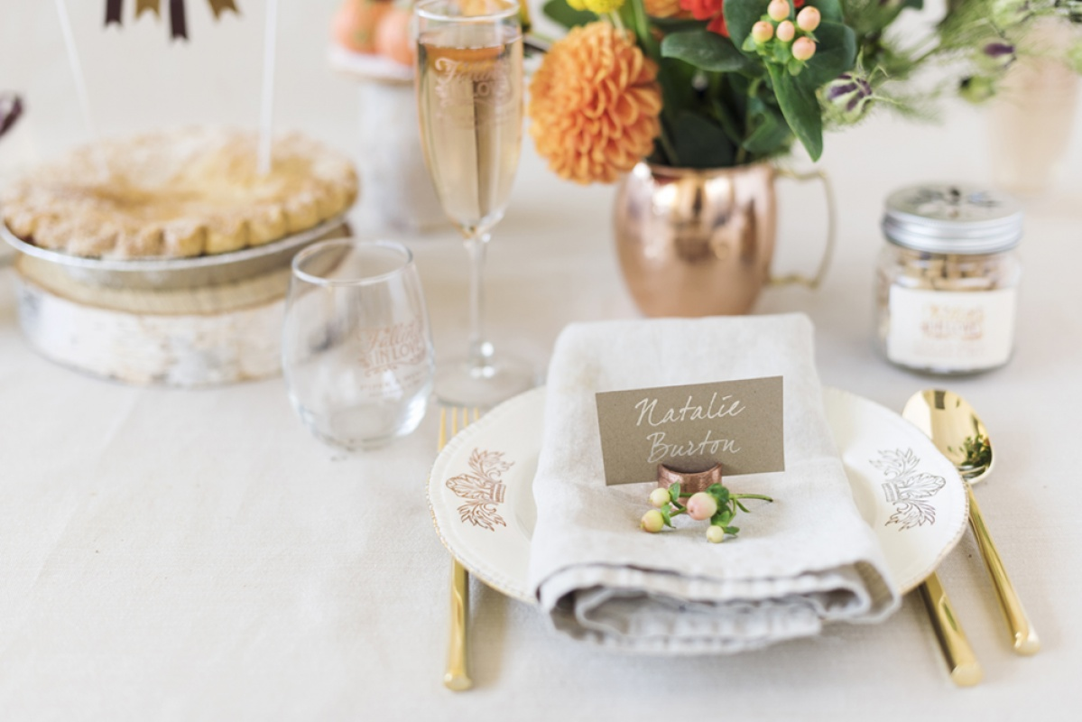 A fall wedding table setting with orange flowers, a copper mug, a champagne glass, a stemless wine glass, pie, a place card, and a copper, white and gold color scheme.