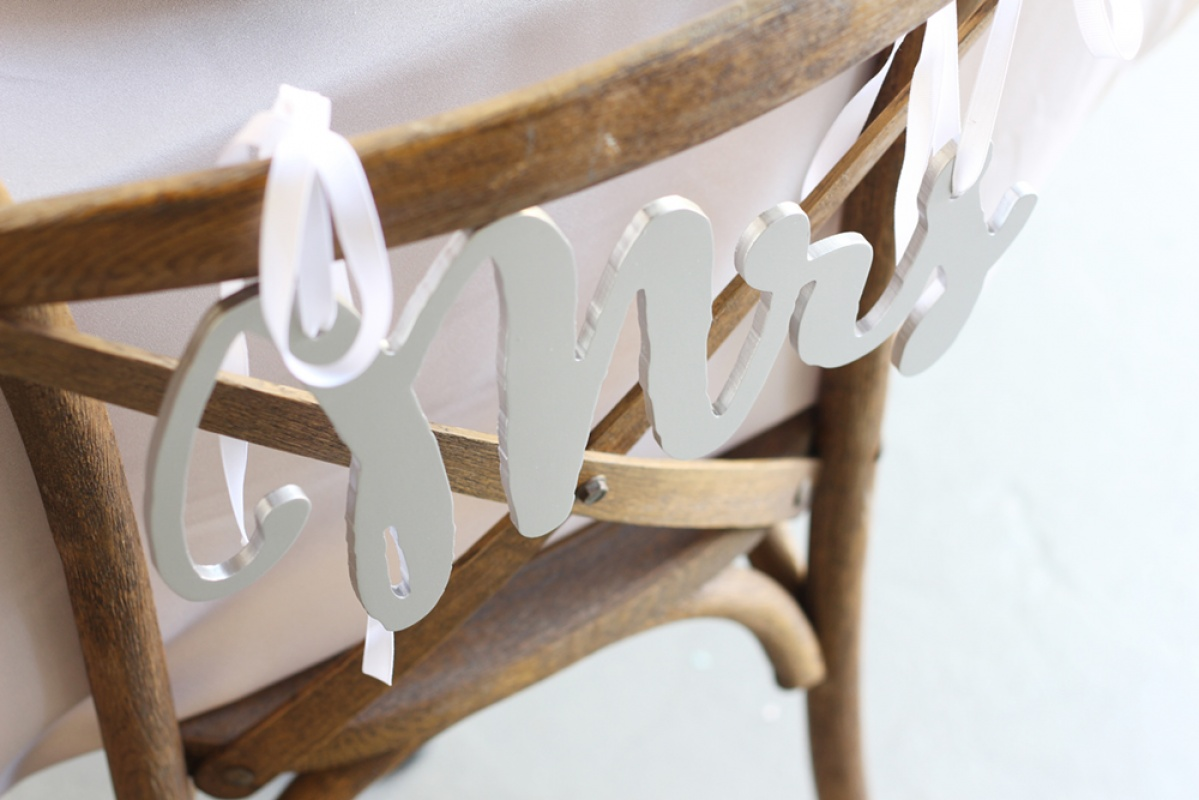 Mrs. chair sign tied on the back of a wood chair for a wedding, bridal shower, or engagement party.