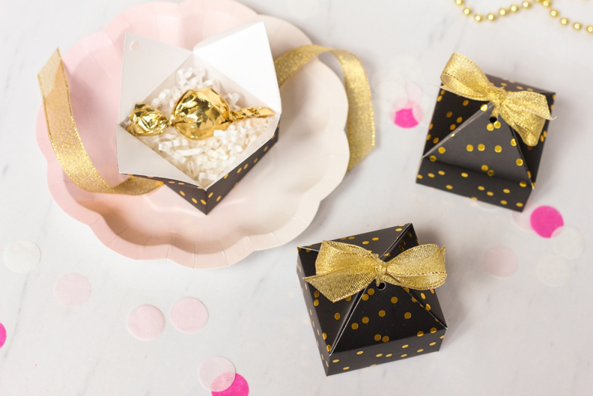 Black and gold polka dot favor boxes with gold ribbon, gold candy, pink confetti, and pink scalloped paper plates.