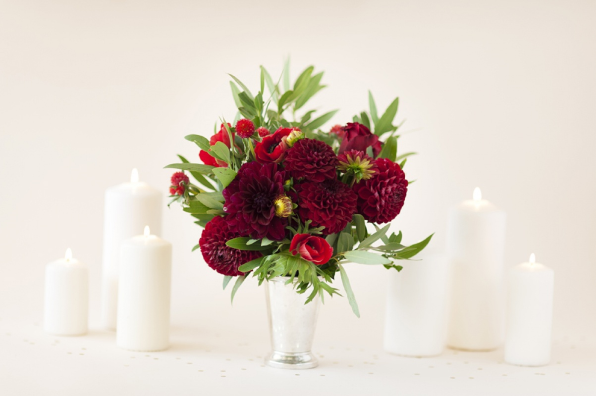 Red wedding flowers including red dahlias and red roses in a vase with white candles.