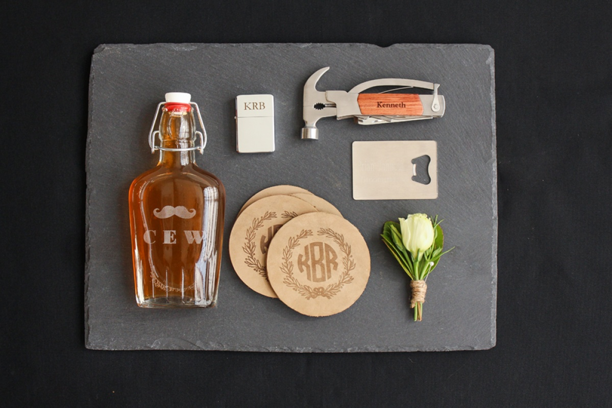 Groomsmen gift ideas flatlay including a personalized monogram bottle, a personalized monogram lighter, a credit card bottle opener, personalized monogram coasters, and a personalized multi tool pocket knife.