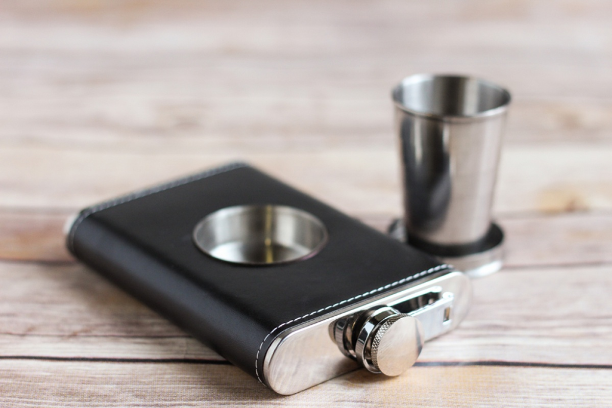 A black leather flask and silver shot glass for a groomsmen gift.