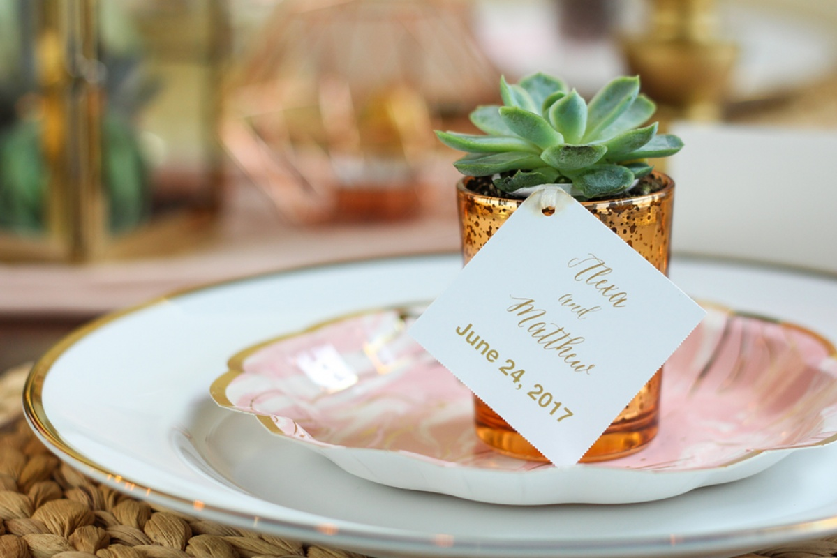 A succulent wedding favor in a copper votive or vase with a personalized tag for a bohemian wedding.