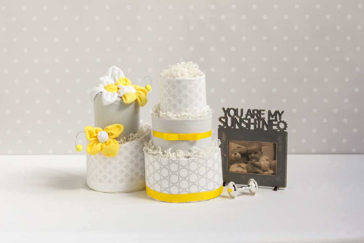 Baby shower gift ideas including a diaper cake, picture frame, flower socks, and blankets.