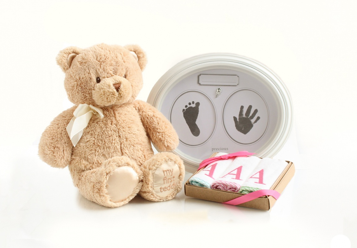 Baby shower gift ideas including a teddy bear, personalized cloths, and a precious prints frame.