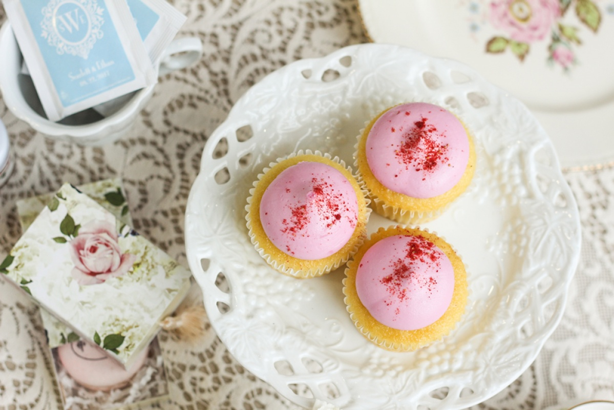 Pink cupcakes on a white plate with floral favor boxes and a lace tablecloth for a tea party bridal shower dessert.